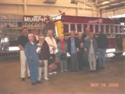 A group of senior citizens standing in front of a fire truck.